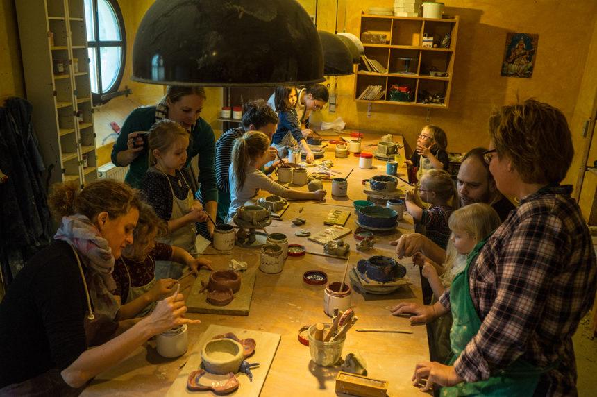 Eltern und Kinder basteln mit Ton an einem großen Tisch