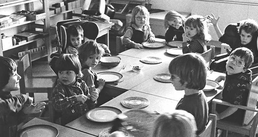 Kinder mit und ohne Behinderung am Esstisch im Kindergarten