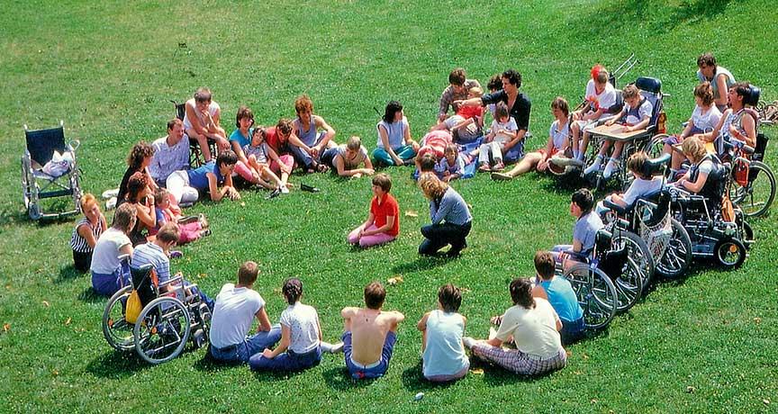 Erwachsene und Jugendliche mit und ohne Behinderung auf der Wiese im Kreis sitzend.