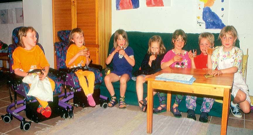 Kinder mit und ohne Behinderung auf dem Sofa nebeneinander sitzend.