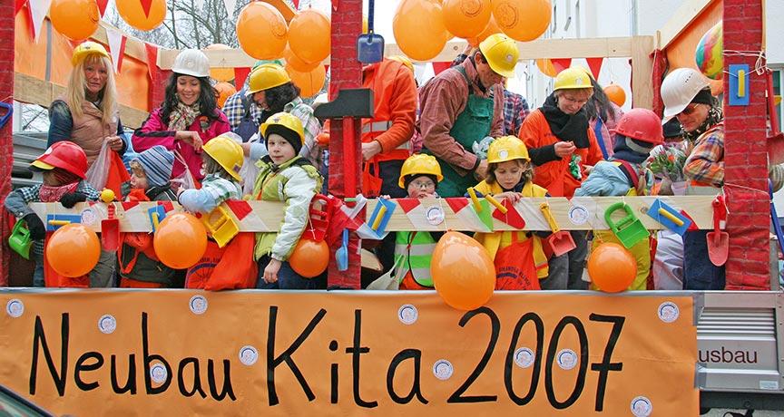 """Kinder und Betreuer mit Luftballons und Bauhelmen und einem Banner mit Aufschrift """"Neubau Kita 2007"""""""
