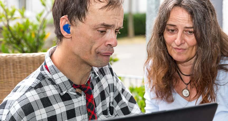 Behinderter Mann mit Betreuerin am Computer.