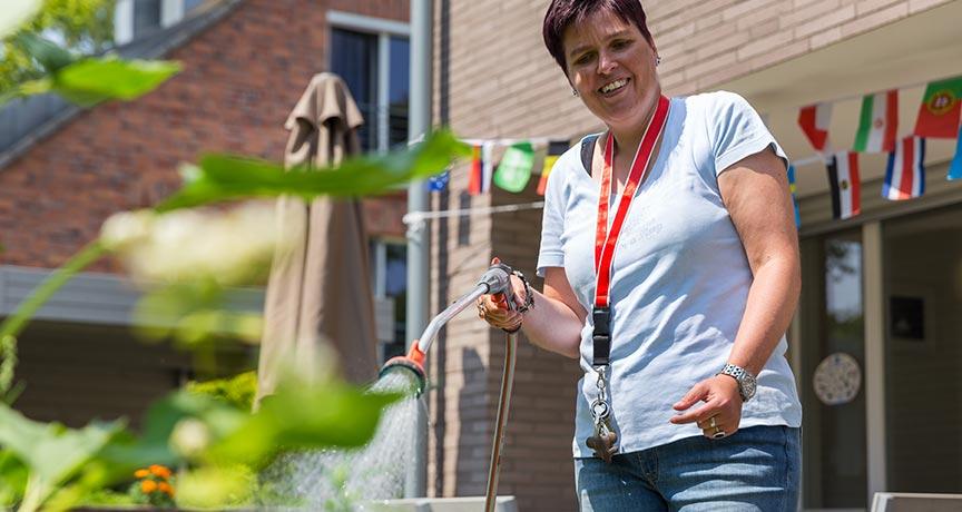 Behinderte Frau beim Blumen gießen.