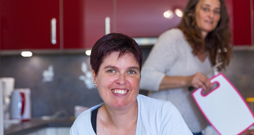 Behinderte Frau lächelt, im Hintergrund eine Bewohnerin in der Küche.