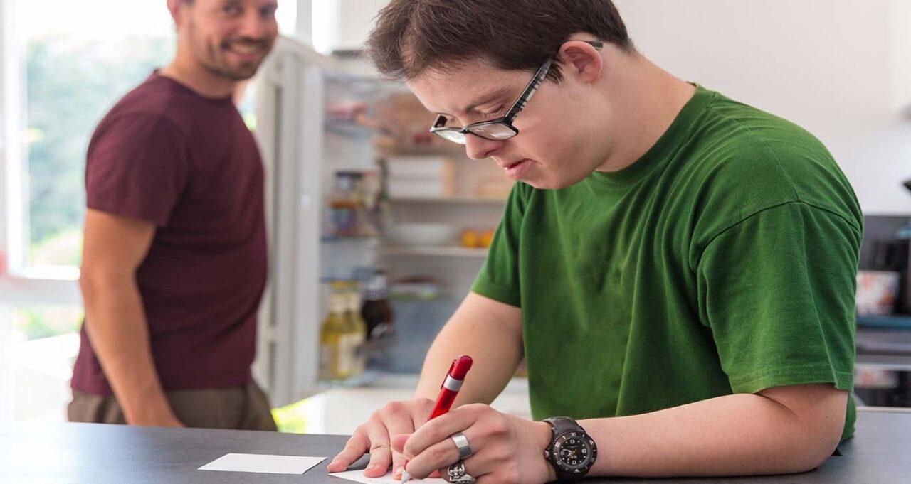 Behinderter Bewohner schreibt auf einen Zettel