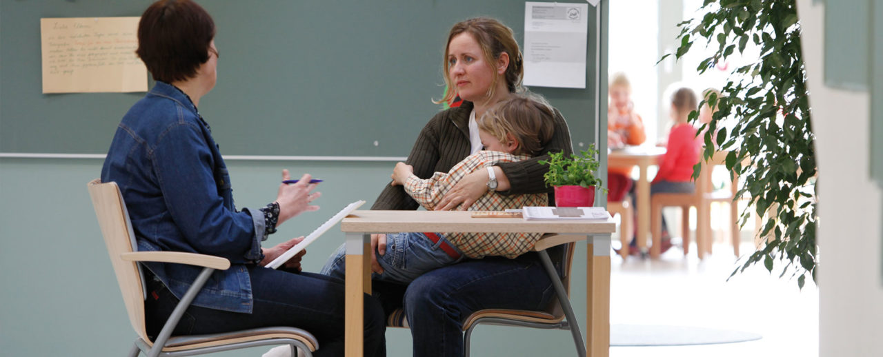 Mutter hält ein Kind im Arm und hört einer Beratung zu
