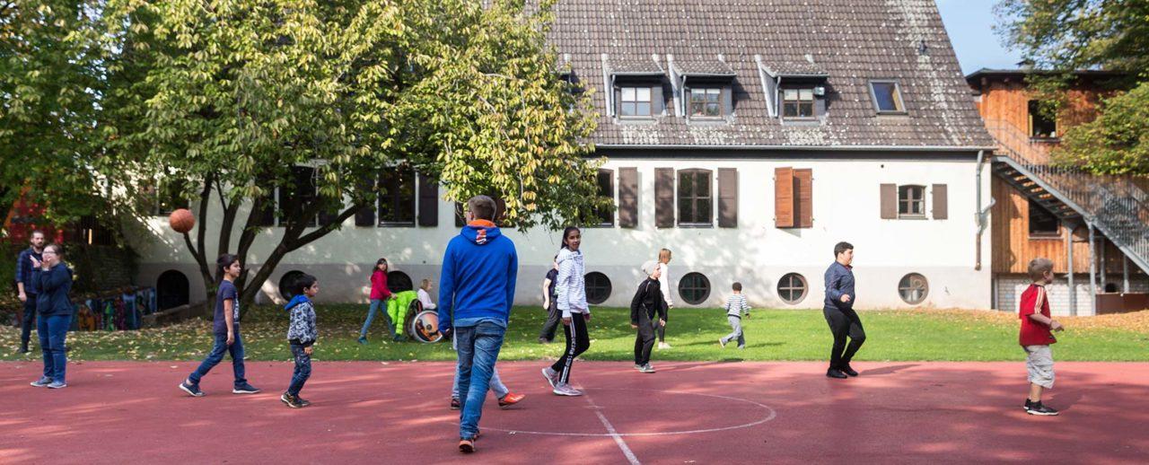 Kinder spielen Basketball auf dem Sportplatz vor dem Jugendhaus