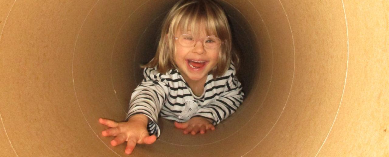 ein behindertes Mädchen krabbelt in einer Röhre