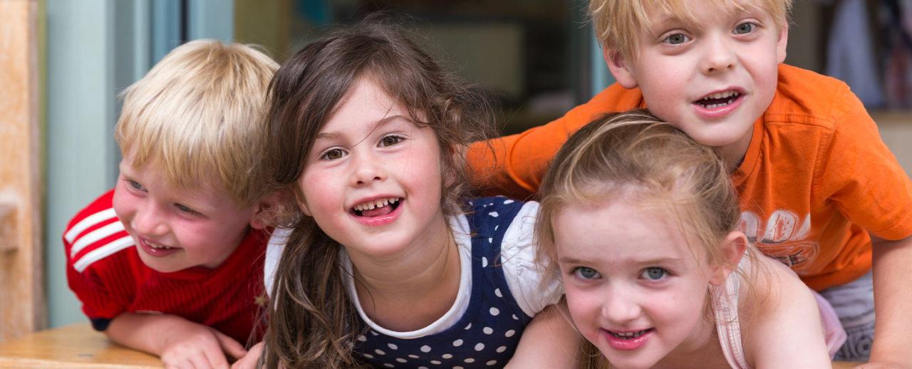 Zwei Jungen und zwei Mädchen auf einem Tisch gelehnt lächelnd