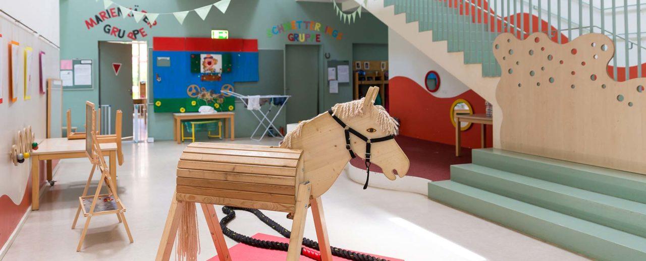 Holzpferd in einer inklusiven Spielgruppe mit verschiedenen Spielsachen