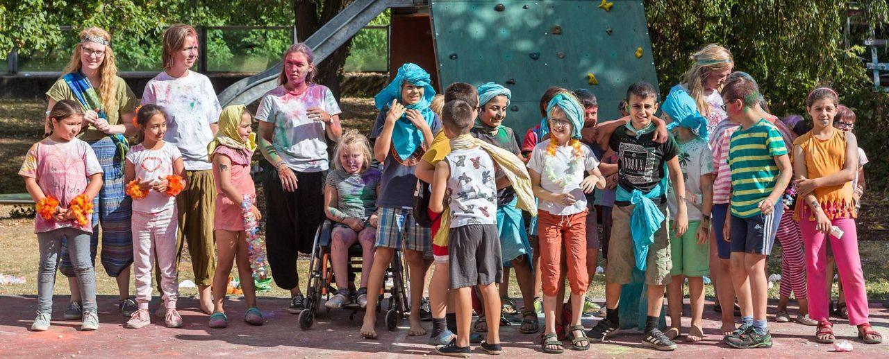 Kinder und Erwachsene in bunter Kleidung und mit buntem Pulver im Gesicht