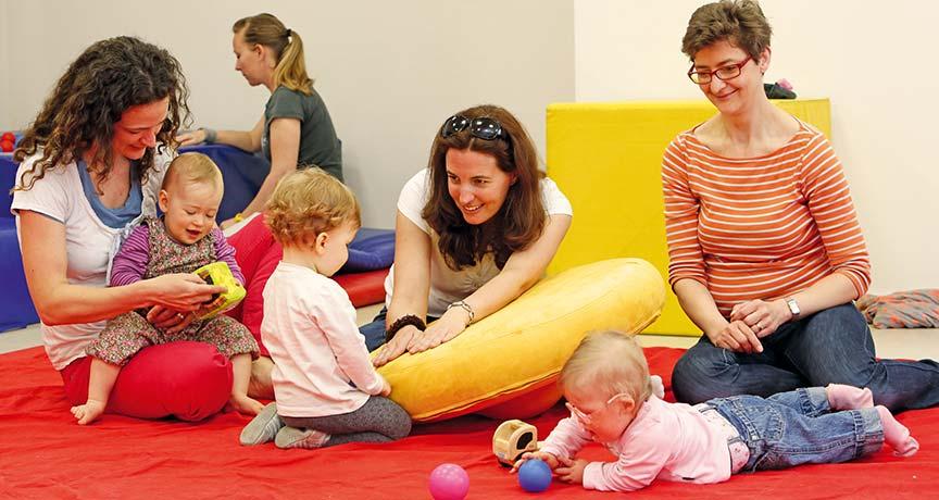 Eltern und Kleinkinder spielen auf einer Decke zusammen