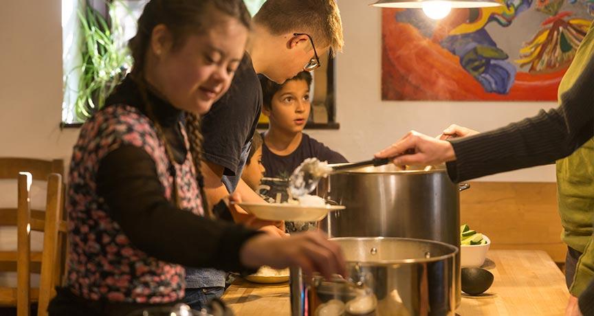 Mädchen und Jungen beim Kochen in der Küche des Jugendhauses