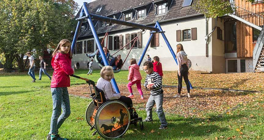 Ein Mädchen schiebt ein anderen im Rollstuhl über die Wiese auf dem Spielplatz