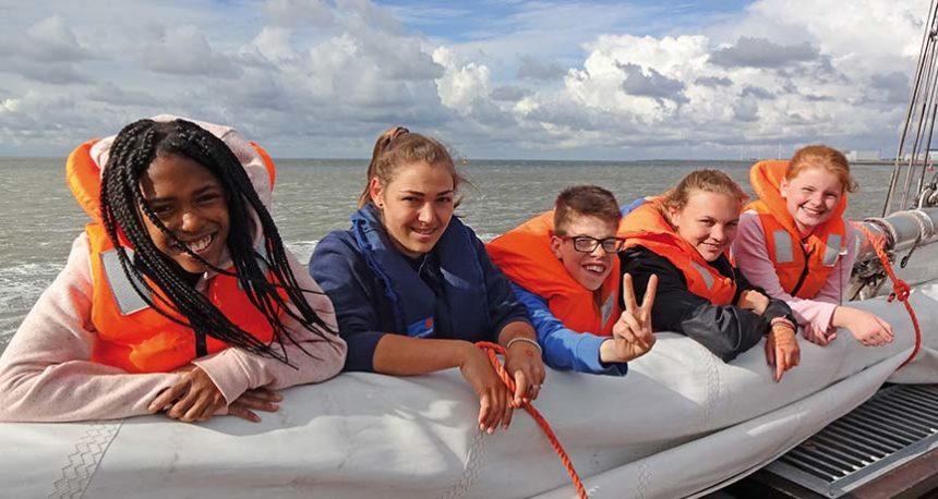 Jugendliche mit Schwimmvesten auf einem Boot im Wasser