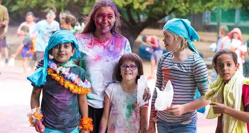 Kinder mit bunten Pulver in Gesicht, Haaren und Kleidung