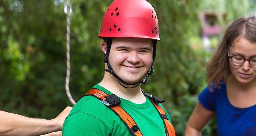 Behinderter Junge mit Helm beim Klettern