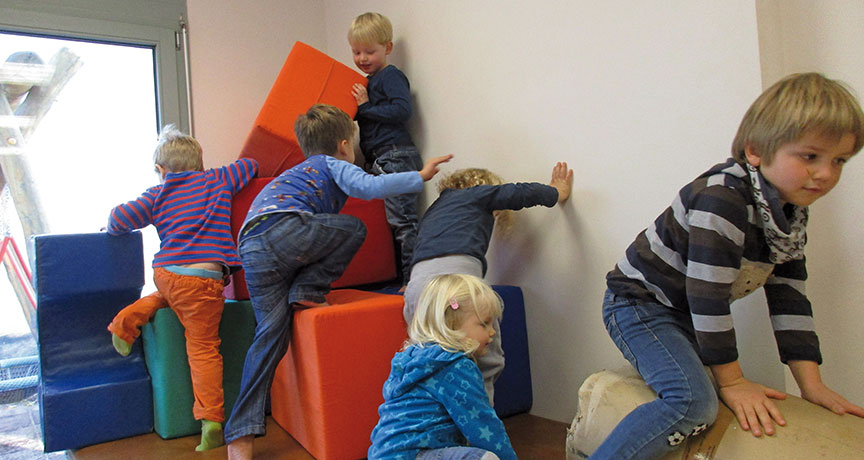 Kinder spielen auf großen eckigen Kissen