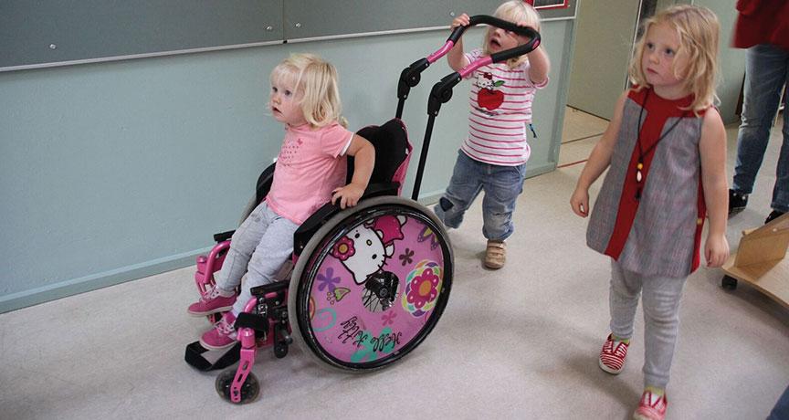 Ein nicht-behindertes Kind wird im Rollstuhl von einem anderen Kind geschoben.