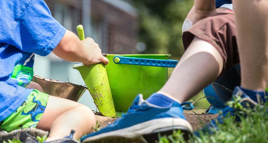 Kinder spielen mit Schaufel und Eimer auf einer Wiese