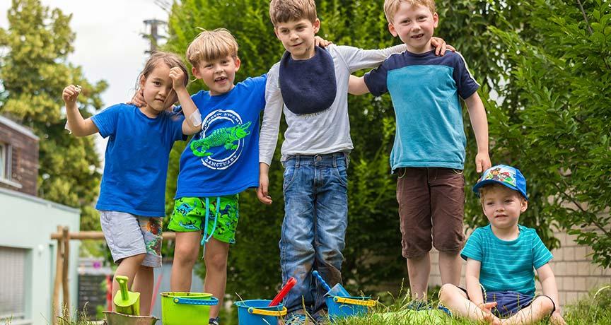 Kinder stehen auf einer Wiese mit Schaufeln und Eimern vor sich und legen die Arme auf die Schultern