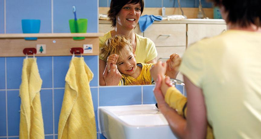 Eine Betreuerin übt mit einem Kind vor dem Spiegel im Bad