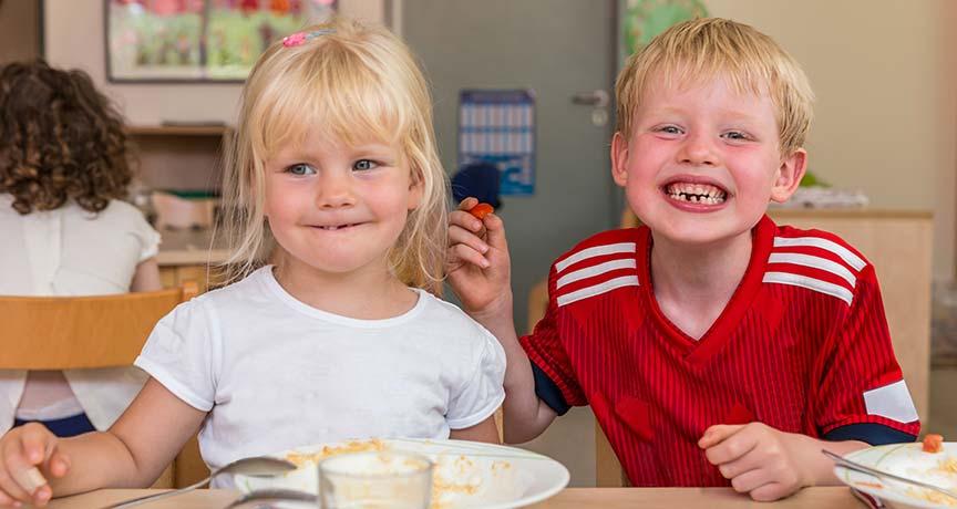 Ein Mädchen und ein Junge sitzen am Tisch und essen.