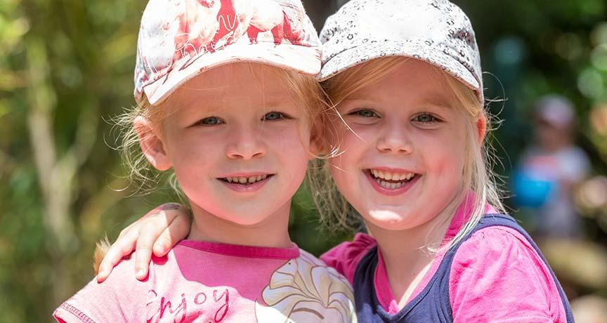 Zwei Mädchen mit Hüten umarmen sich und lächeln in die Kamera