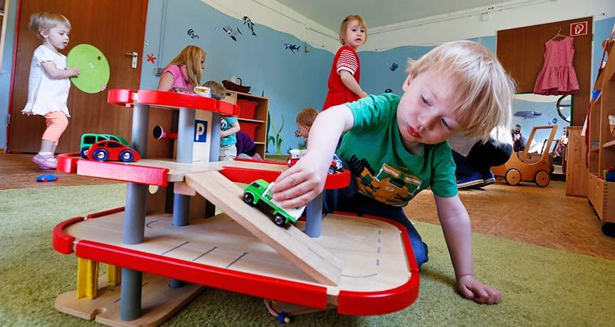 Junge spielt mit einem Spielauto auf einer Holzgarage