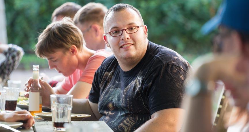 Behinderter junger Mann beim gemeinsamen Essen.